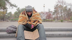Poor man asking for charity in city park, miserable homeless person needs help Stock Footage