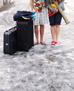 Couple standing in snow with suitcases Stock Photos