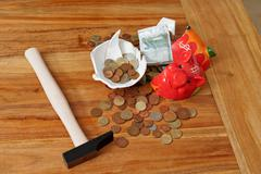 Smashed piggy bank with euros and hammer - stock photo