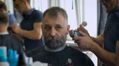 A respectable businessman with a white beard in the salon for hair.  Stock Footage