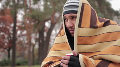 Poor man with sad face hiding from cold in shabby blanket, warming with hot tea Arkistovideo