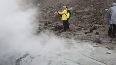 Tourists walk and photographing in crater active volcano Stock Footage