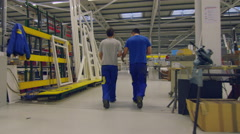 Two members of staff walking and talking while passing through the factory Stock Footage