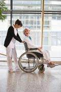Old woman in a wheel chair and nurse Kuvituskuvat