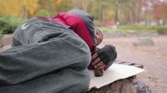 Unlucky drunk man falling asleep on the bench in city park, addiction to alcohol Stock Footage