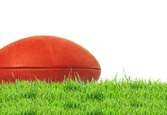 American football (rugby ball) on green grass over white, close up Kuvituskuvat