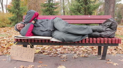 Needy male sleeping on bench in autumn park, homeless man waiting for help Stock Footage