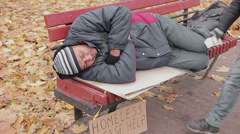 Anonymous benefactor giving generous charity donation to sleeping homeless man Stock Footage