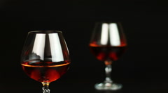 Glass of brandy over black background Stock Footage