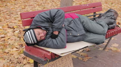 Lonely poor man lying on bench, miserable bum suffering from hunger and cold Stock Footage
