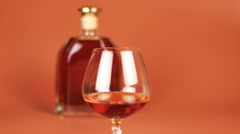 Bottle and glass of brandy on brown background Stock Footage