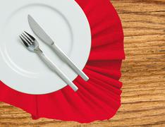 Fork, knife and white plate on a red cloth on wooden table Stock Photos