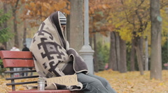 Lonely poor person sitting on bench, warming up with old blanket, man starving Stock Footage