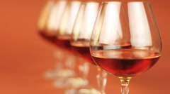 Glass of brandy over brown background - stock footage