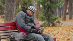 Male alcohol addict having a nap on bench in autumn park with bottle in hand Stock Footage