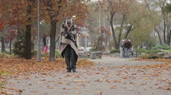 Miserable poor man walking in city park covered from cold with shabby blanket Stock Footage