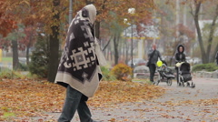 Unhappy beggar limping in autumn park, social vulnerability and poverty problem - stock footage