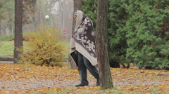 Lonely poor man limping in park, strange man covered with blanked needs help Stock Footage