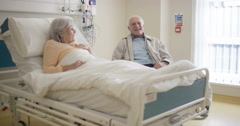 4K Senior couple in hospital room, man visiting sick wife & chatting with her Stock Footage