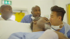 4K Hospital emergency team rush a patient on a gurney to operating room Stock Footage