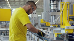 Factory worker sorting out his machine Stock Footage