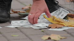 Street cleaner sweeping dollar banknotes in city street, money losing value Stock Footage
