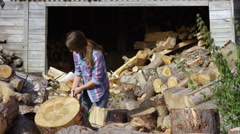 Lady farmer cutting wood in the yard Stock Footage