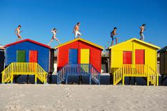 Group running on top of beach huts - stock photo