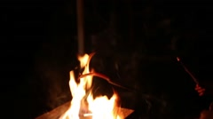 Fire in roaster and hot poker in hands of children at night Stock Footage