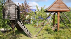 Empty wooden swing and small house for kids in garden at summer Stock Footage