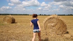 Woman in shorts poses near baled hay on mown field at summer Stock Footage