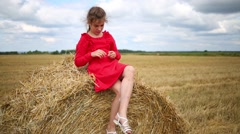 Girl in red sits on yellow baled hay on mown field at summer Stock Footage