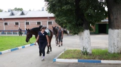 Women lead horses in Stable of horse squadron of police to patrol Stock Footage