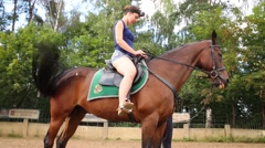 Woman sits on horse with emblem on seat and prepares for riding - stock footage