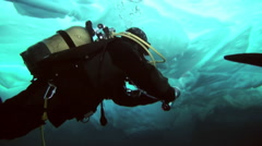 Diver under the Arctic ice at the North Pole takes samples of ice. Stock Footage