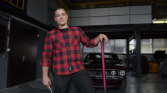 Mechanic standing outside his workshop, while camera pans towards him Stock Footage