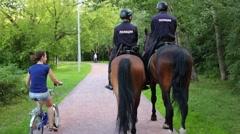 Back of two horse policemen and woman rides bike in park Stock Footage