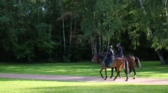 Two horse policemen rides in park - special police squadron patrols Stock Footage