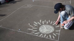 Unrecognizable boy in cap draws with chalk Sun on pavement Stock Footage
