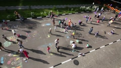 Top view of children, parents drawing with chalk on pavement Stock Footage