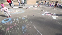 Children draw by chalk on pavement in Elk Island residential complex Stock Footage