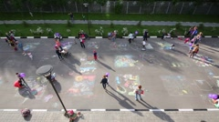 Top view of children and parents drawing with chalk on pavement Stock Footage