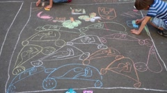 Unrecognizable boy and girl draw cars by chalk on asphalt. Stock Footage