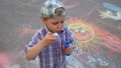 Handsome little boy blows bubbles and stands on asphalt Stock Footage