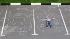 Girl lies on big butterfly drawn by chalk near draw car on asphalt Stock Footage
