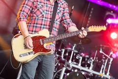 rock musician strumming an electric guitar - stock photo