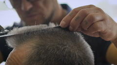 Gray-haired man in a barber shop. Hairstyle is almost ready, Barber leveled Stock Footage