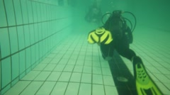 Two divers in wetsuits with scubas swim on bottom of pool Stock Footage