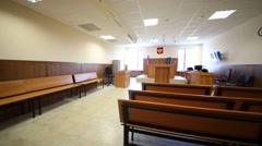 Interior of empty courtroom with benches, flag and emblem Stock Footage