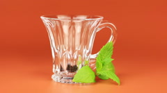 Tea is poured into a glass cup and mint leaf on brown background. - stock footage